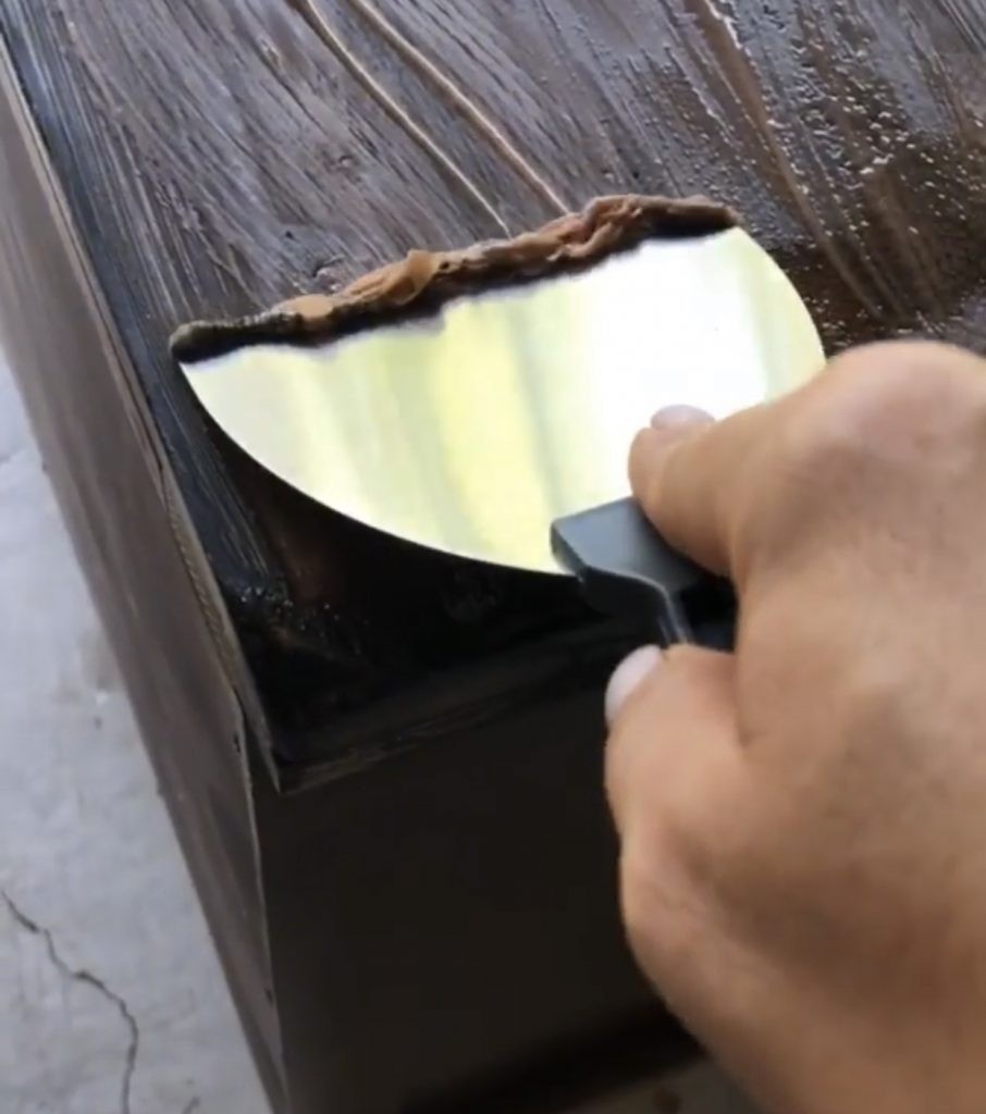 Using a metal scraper to remove the Citristrip and stain.
