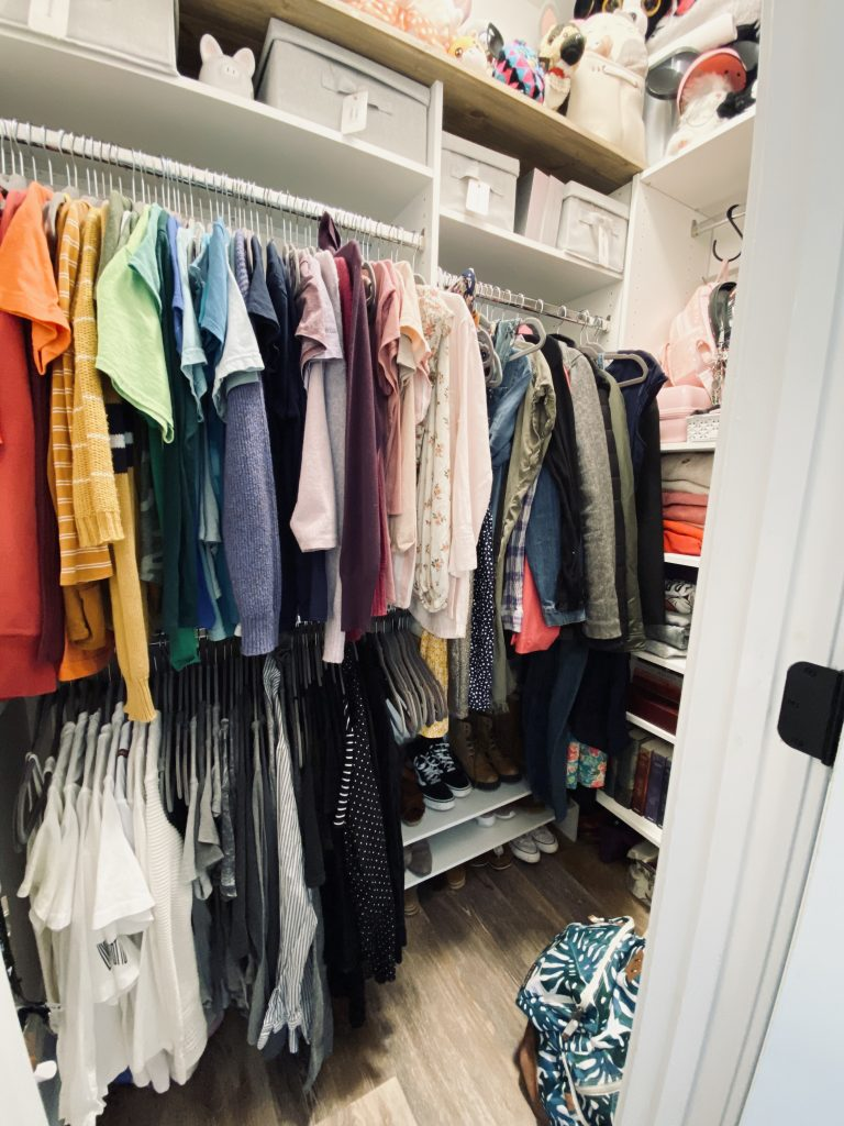 Walk in closet with short and long hanging clothing items on the left. Shoe rack on the floor with multiple pairs of shoes organized. Shelving to the right with folded clothing items and books.