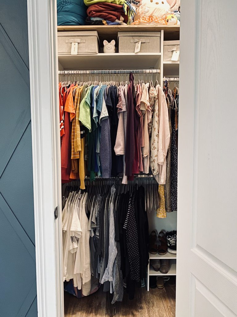 Two tiered closet hanging system with clothes hung in rainbow order.