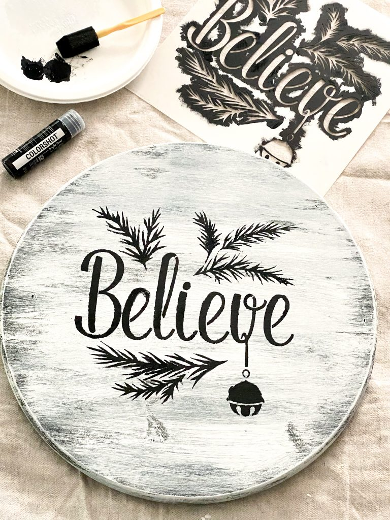 "White painted wood round with the words ""Believe"" branches, and bell in black. Above wood round to the upper right is the used stencil. To the left is a plate with black paint and container of black paint."