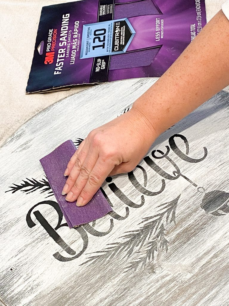 Hand holding purple sand paper on top of black words. Package of sand paper to the right of the white wood round.