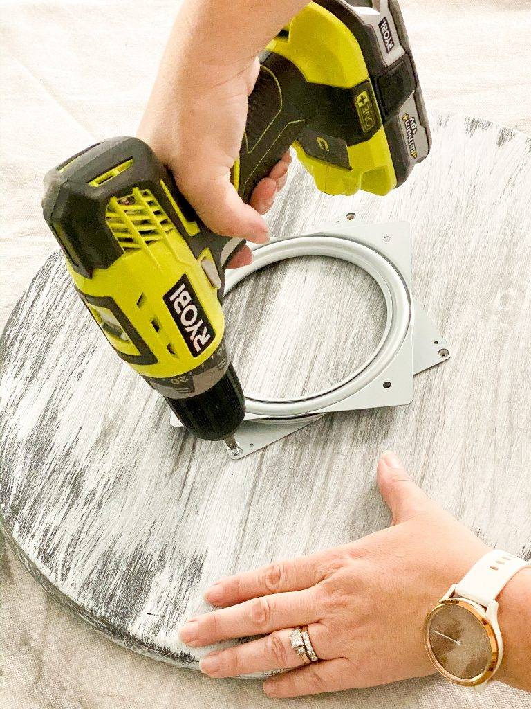 Hand holding green Ryobi power drill inserting a screw in the hole of a metal swivel plate.