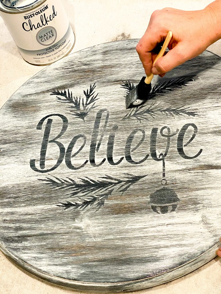 "White wood round painted and distressed with black peeking through. Black words ""Believe"" with branches and bell. Hand holding foam brush applying clear protective coating."