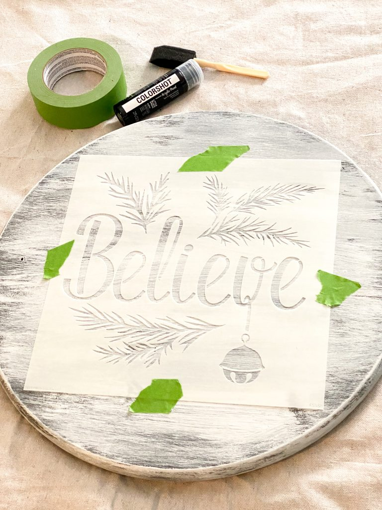 "Painted round wood piece with a stencil that has the words ""Believe"" and branches taped to the wood piece with green tape."