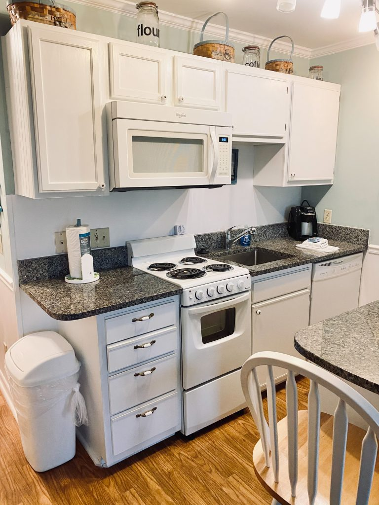 Kitchen with white cabinets, white stove, baskets on top of the cabinets, and brown flooring.