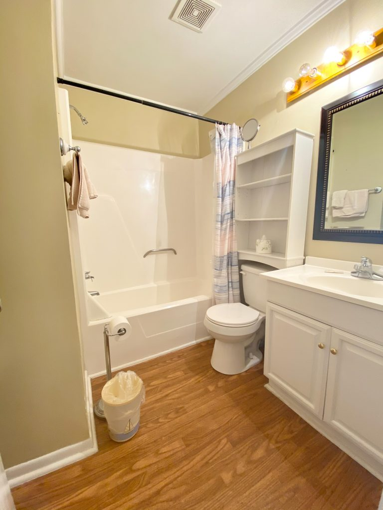 Large beach condo bathroom with shower in background, toilet, and sink on the right.