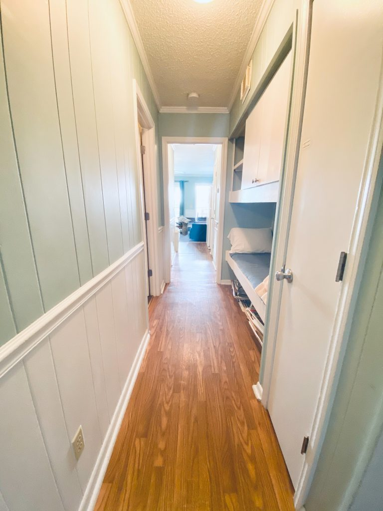 hallway looking from the front door. Painted green paneling on the top and painted white on the bottom. The right side of the hall has built in bunk beds with storage under the beds. Brown flooring.