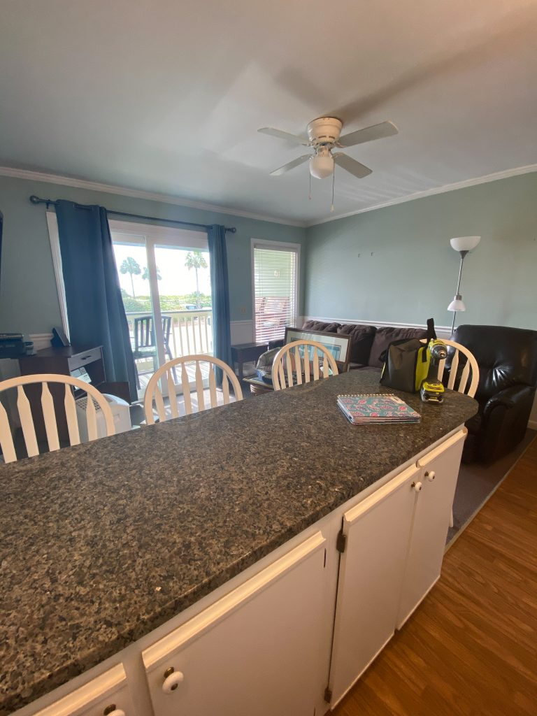Kitchen island with granite counter and chairs on the opposite side. Looking into living room with large brown sofa and blue curtains.