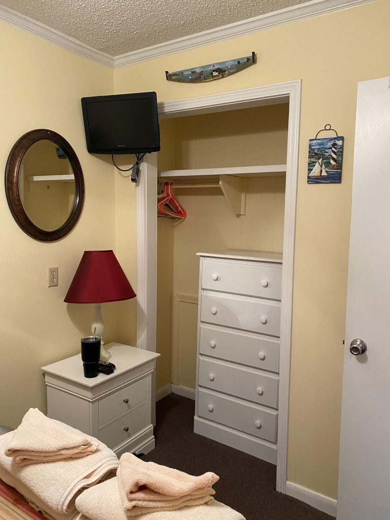 open closet with dresser inside, small tv hanging on the wall to the left with a mirror below that and a small table with lamp under the mirror.