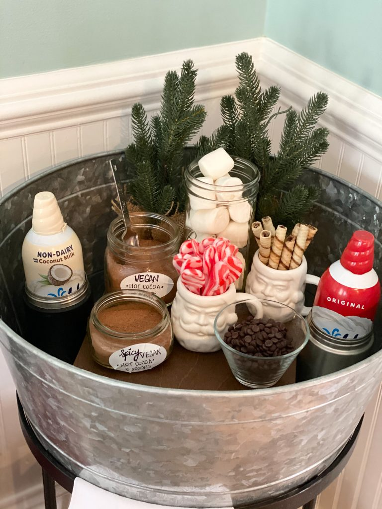 Large metal serving bowl with individual glass containers containing the ingredients to make a vegan hot cocoa. Behind the ingredients are small pine trees.