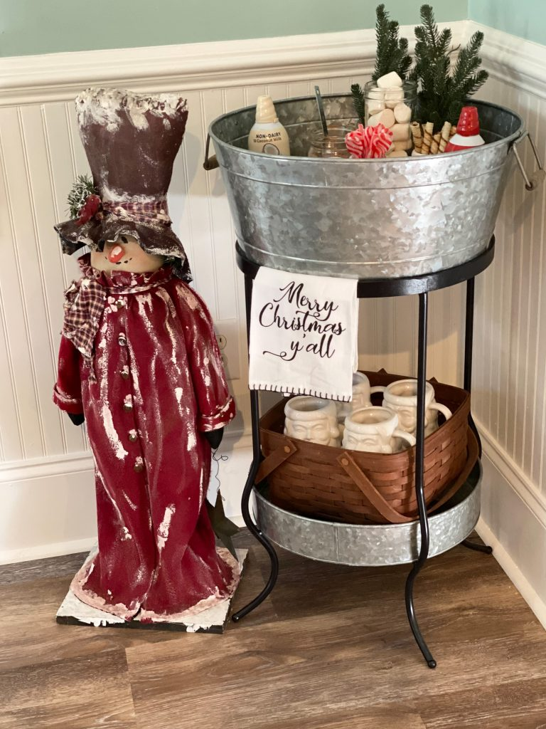 "Snow man in a red coat and brown top hat stand next to a metal beverage stand. Hanging off the front of the stand is a towel that reads ""Merry Christmas Y'all"". In the bottom of the beverage stand is a brown basket with white Santa face mugs. The top fo the beverage stand is a large galvanized tub where all the vegan hot cocoa powder and toppings are displayed."