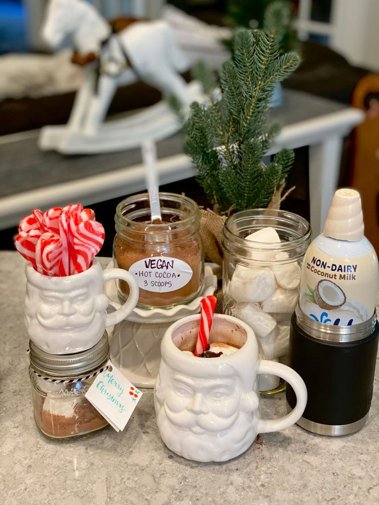 Small white Santa face mug contains peppermint candy spoons sitting on top of a personal sized hot cocoa mix in a glass jar. Surrounded by the vegan hot cocoa mix, a made cup of hot cocoa. Vegan marshmallows are in a jar behind to the right and a can of non dairy cream whip next to it.
