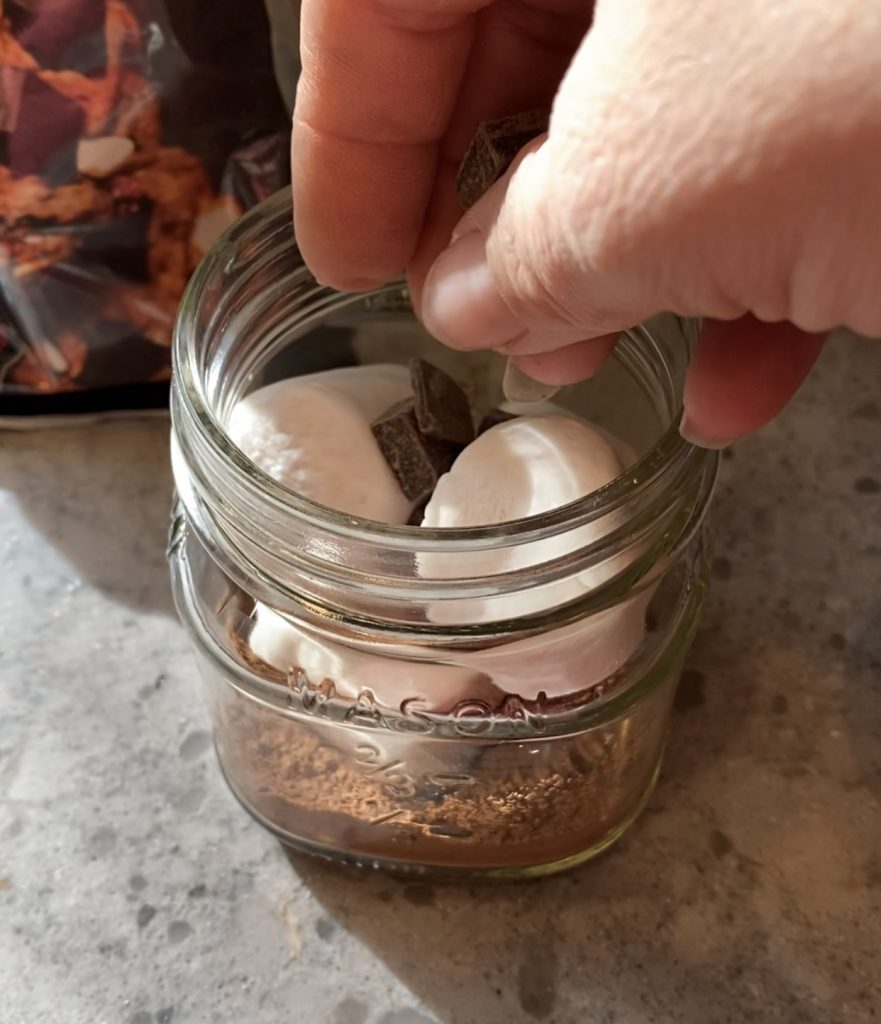 Hand dropping in dark chocolate chips into a small glass jar of hot cocoa mix and vegan marshmallows.