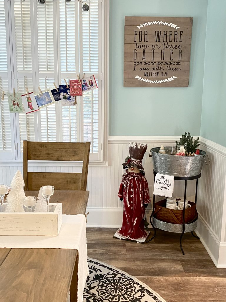 Wide shot of the kitchen area where the snowman and hot cocoa bar are in the corner to the right. To the left is a corner shot of the table, with a wood box on top of the table that holds small bottle brush trees and glass candle sticks. Behind the table Christmas cards hang from a string with clothes pins and all are attached to the plantation shutters on the window.