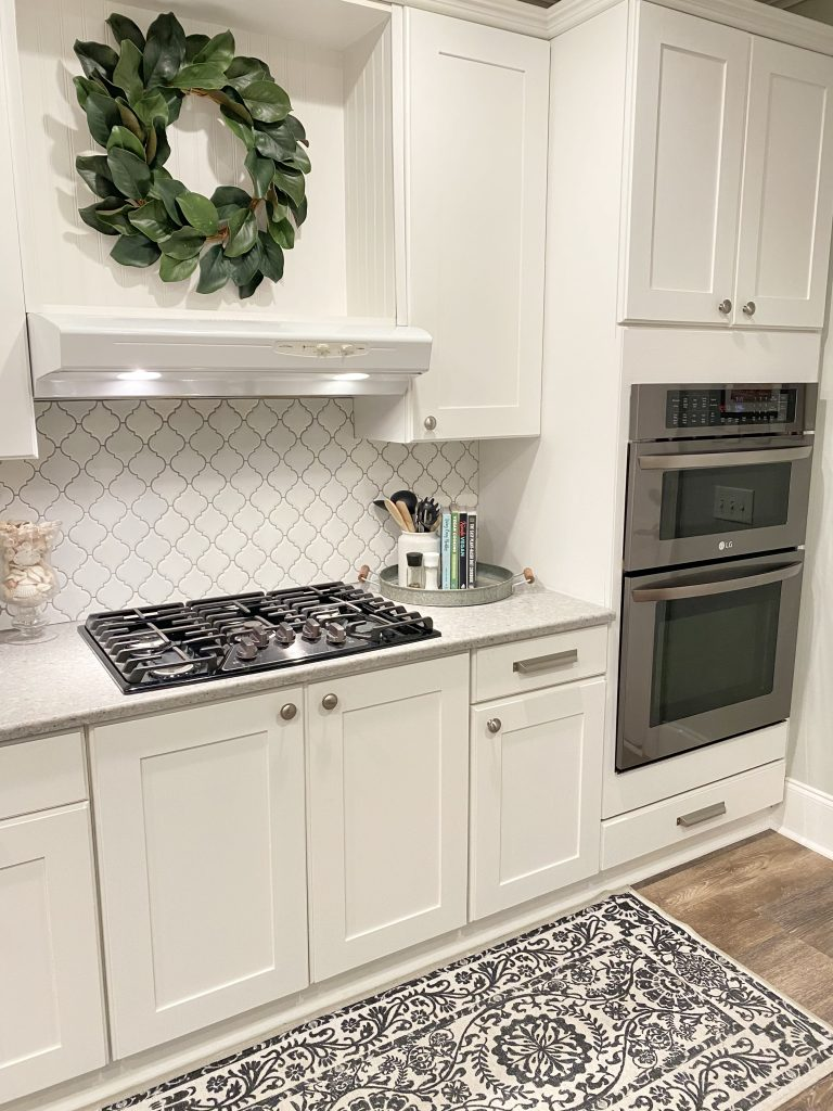 White cabinets, gray counter, and new white arabesque tile with gray grout. Next to cabinets are dark gray stacked microwave and oven. Floor is brown wood looking and a black and white rug with a floral design sits on top.