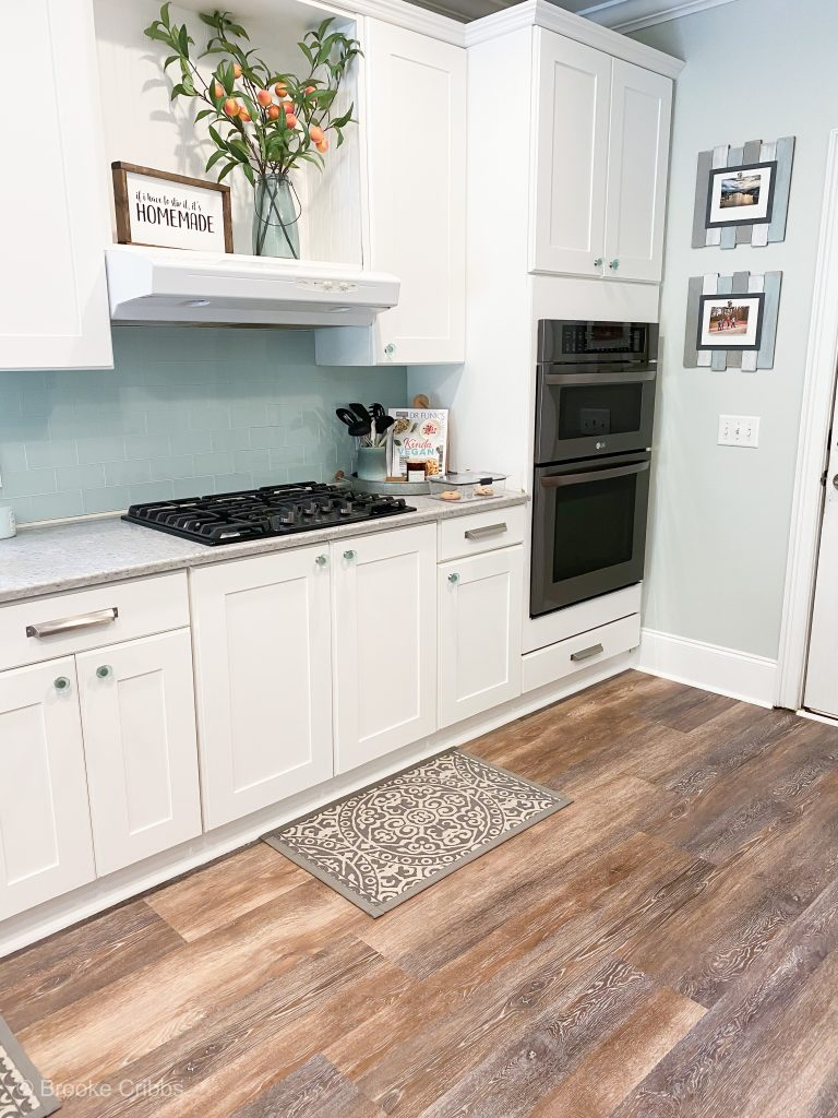 White cabinets on the left with a cook top stove , teal peel and stick tile, brown wood floors