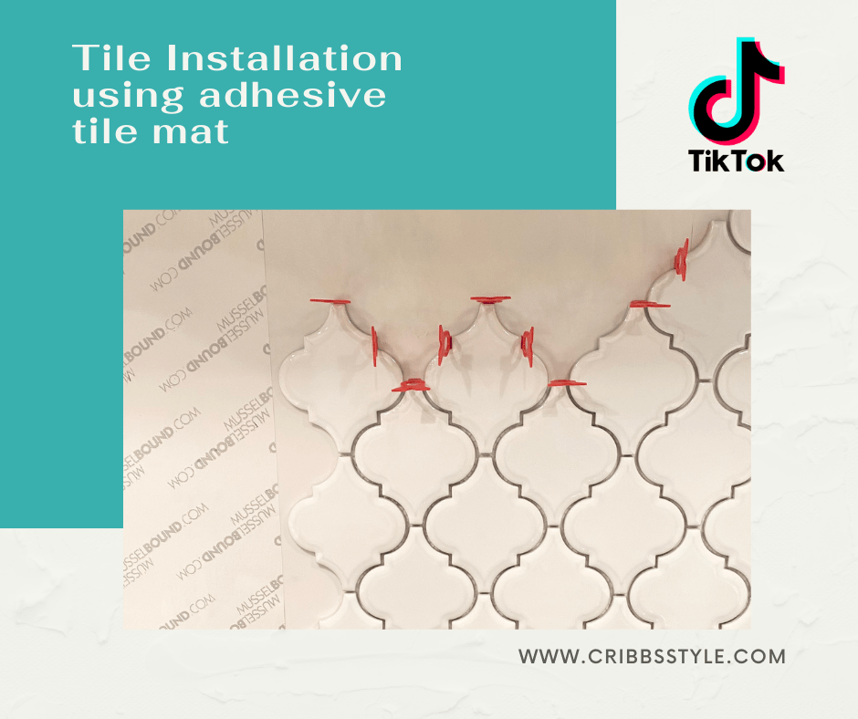 White arabesque tile and red spacers around the top on a white background. Next to the tile is the sticker paper that covers the adhesive mat.