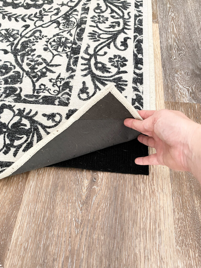 Black and white floral Ruggable washable rug with corner flipped up to show the black pad under all on top of a brown vinyl plank floor.