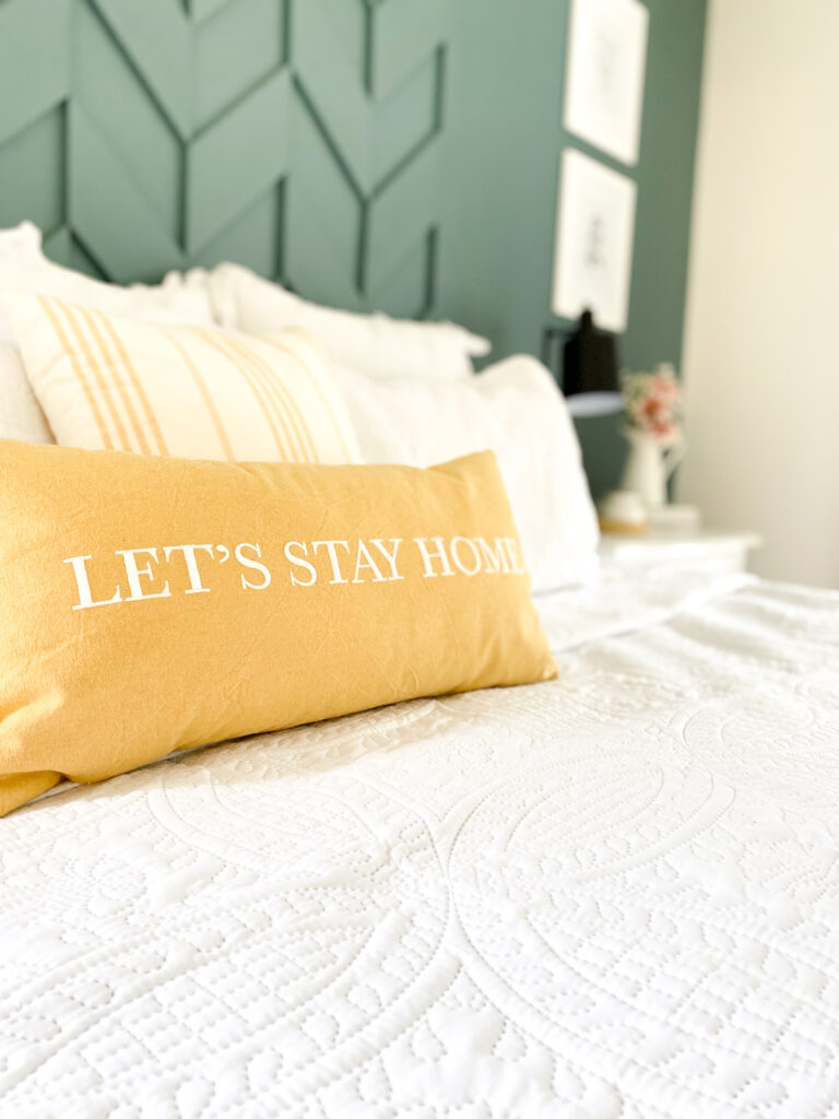 """Green pattern accent wall behind the bed with a couple white pillows and in front is a yellow and white stripped square pillow and a yellow lumbar pillow with the words """"Let's Stay Home"""" embroidered on the front. All on top of white bedding. Next to the bed you see a black lamp on a white side table. Next the the lamp is a white pitcher with pink dahlia flowers . Hanging up on the wall behind the lamp and flowers are two white picture frames."""