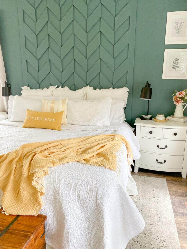 """Green wall with woven wood accent behind a bed with all white bedding. A square yellow stripped pillow sits in front of many all white pillows and in front of that is a long yellow pillow with the words """"Let's Stay Home"""" embroidered on the front. Next to the bed is a white three drawer dresser with a black lamp. Next to the lamp is a white candle in a brown basket. Next to the candle is a white pitcher with pink dahlia's. Hanging on the wall above the tale are to white picture frames with black sketches of flowers. At the end of the bed is a yellow blank and under the bed is a gray and white pattern rug."""