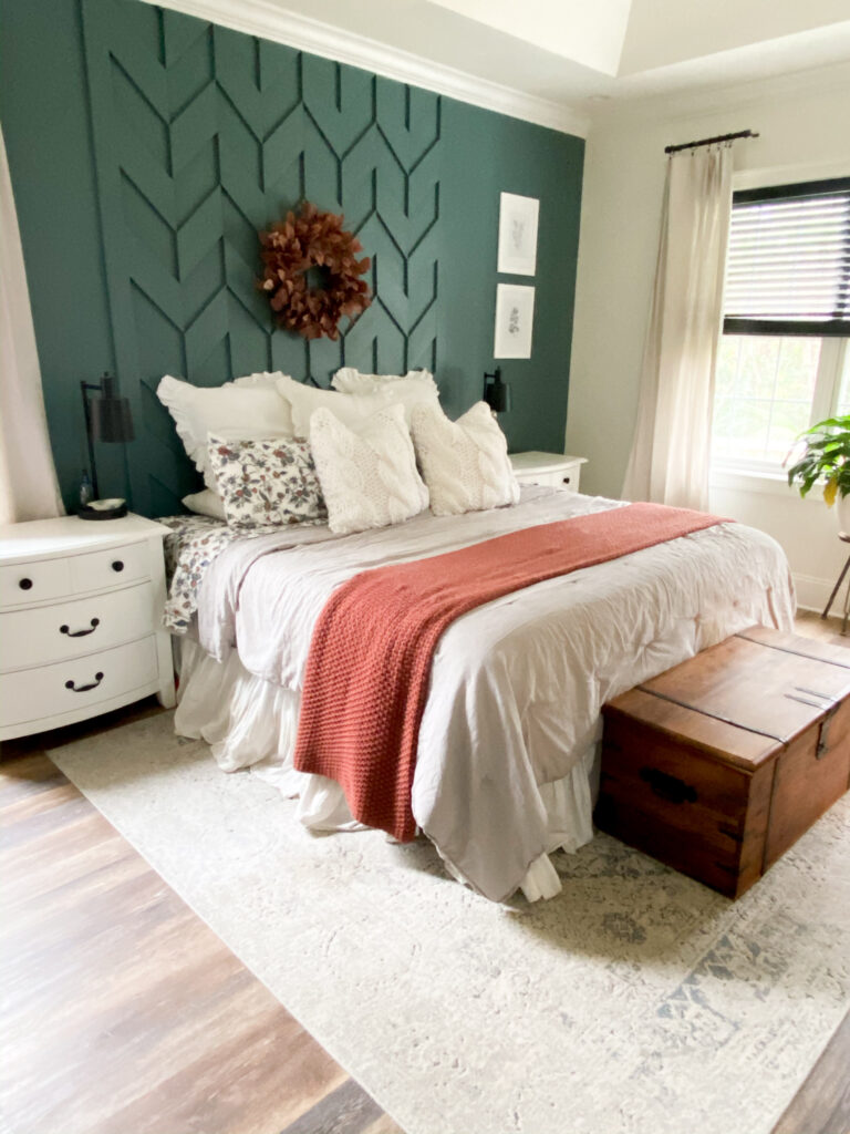 Dark green wall with woven wood accent and a rust colored wreathe hanging in the middle. I In front of wall is king sized bed with three large white pillows, patterned sheets, two white pillows and a gray comforter. Folded at the end of the bed is a rust covered blanket. On either side of the bed are white 3 drawer nightstands with a black lamp. Under the bed is a gray and white designed rug. At the end of the bed is a brown wood trunk. The wall next to the bed has windows and a plant placed in the middle.