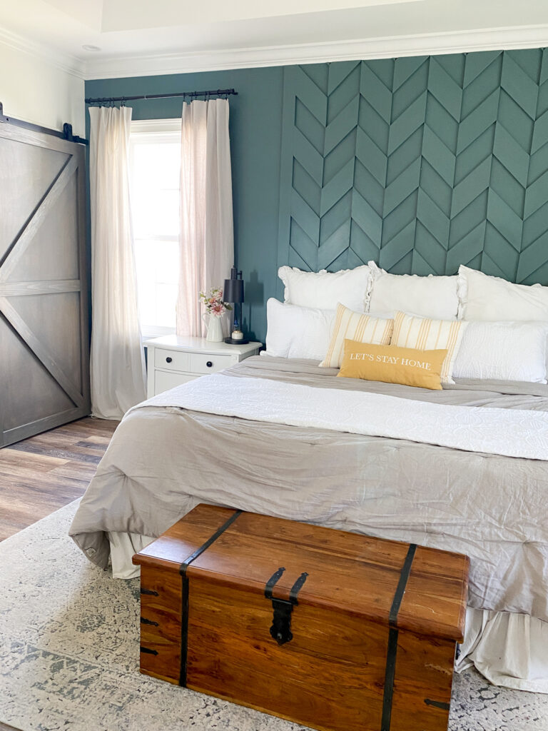 """Green woven accent wall behind bed with three large square white pillows, in front two long white pillow. In front of those are two square yellow and white stripped pillows and in front of that is a long yellow pillow with the words """"Let's Stay Home"""" embroidered on the front. There is a gray bedspread and folded at the end of the bed is the white coverlet. To the left of the bed is a white three drawer nightstand that has a black lamp and white pitcher with pink dahlia's. Next to the table is a window with long curtains and next to the window you can see a gray barn door. At the food fo the bed you can partially see a brown wood trunk."""