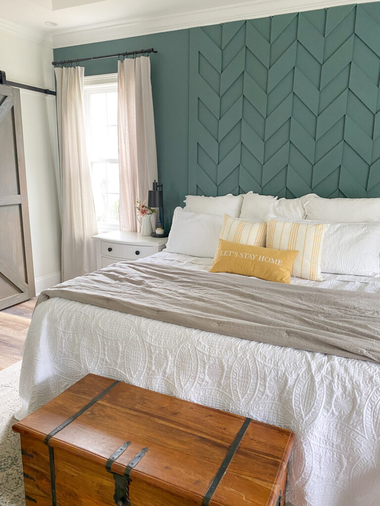 Same as the image above except at the end of the bed there is a folded gray comforter. At the end of the bed is a brown wooden trunk. To the left of the bed is a gray wood barn door.
