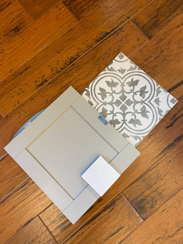 gray cabinet door sample next to dark gray and white tile sample