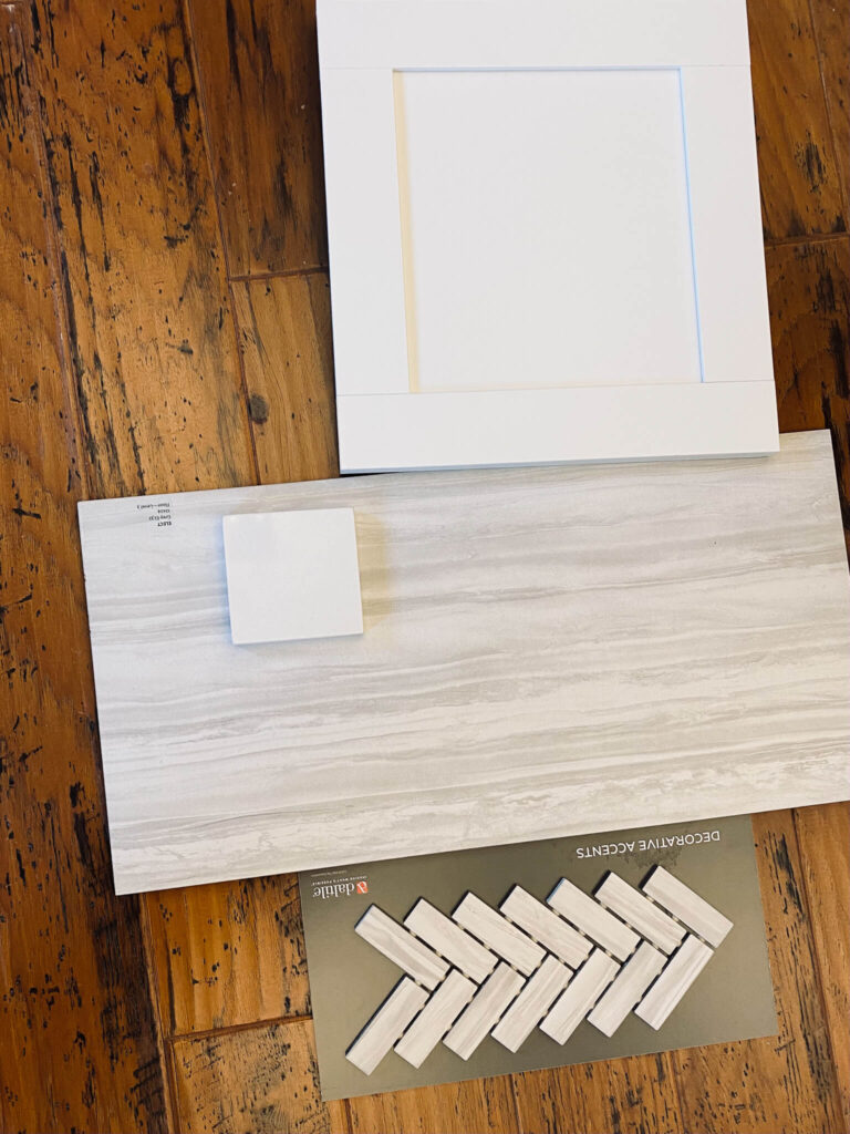 white cabinet sample at the top of the photo, under is a gray and white large tile sample and under is a tile sample showing a small herringbone pattern