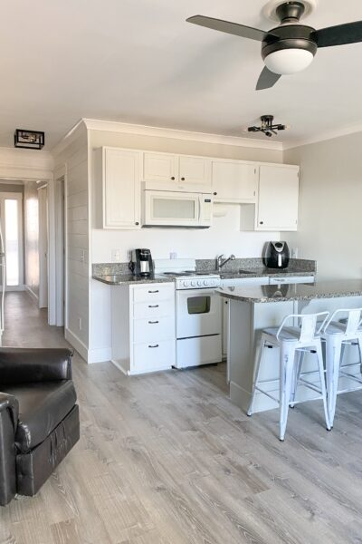 white kitchen cabinets with black counter tops. Black ceiling fan with black lighting fixtures. white metal counter height bar stools, gray wood floors. black recliner to the left.