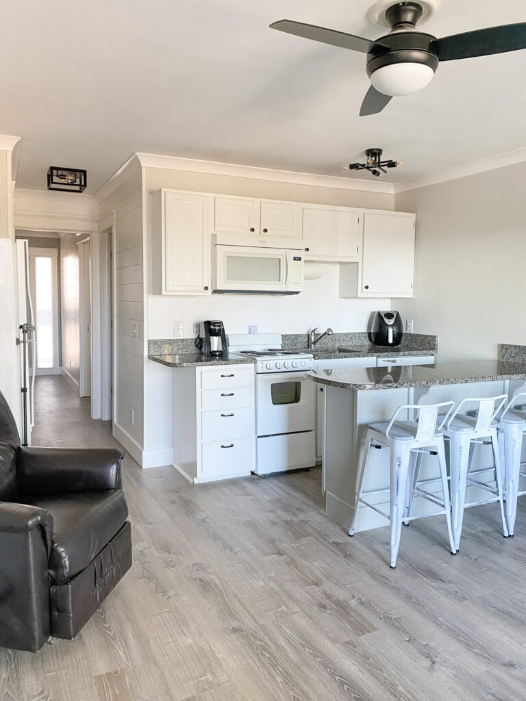 White kitchen with gray wood floors and black ceiling fan.