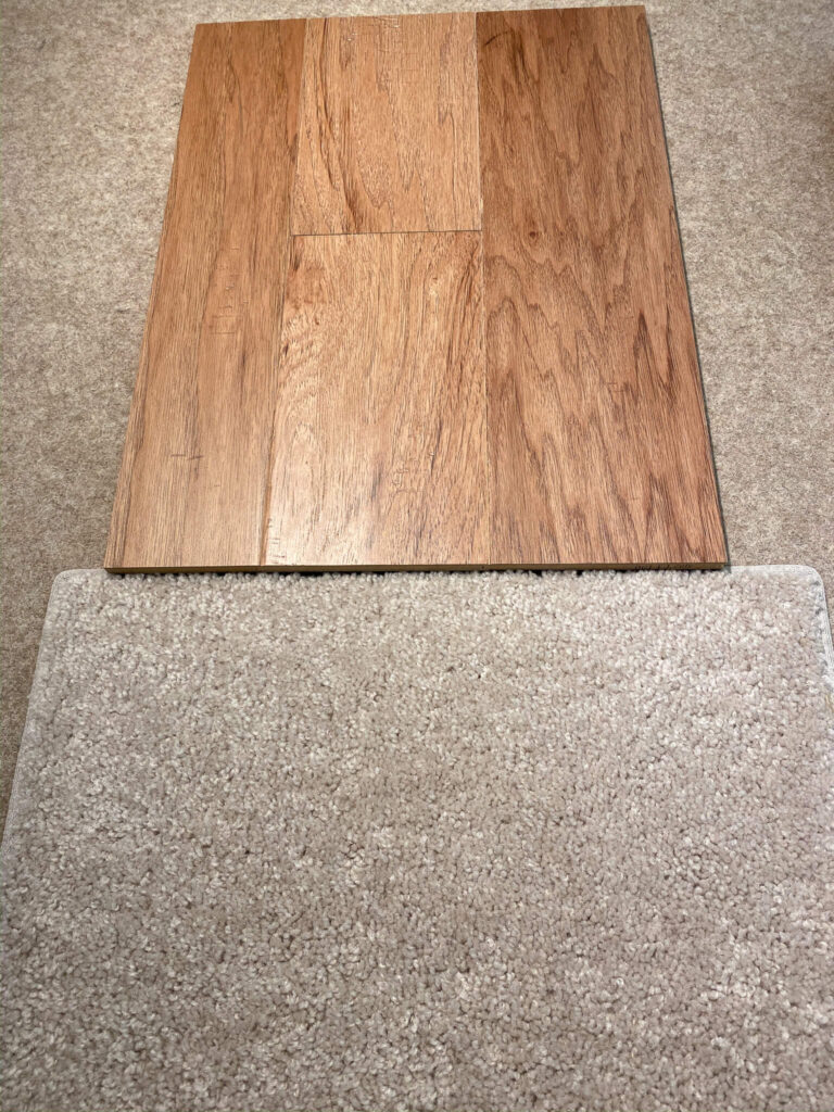 light brown wood flooring sample at the top with light beige carpet under