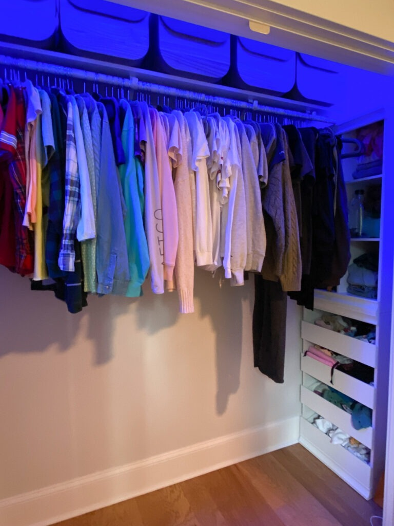 Closet with one row of hanging clothes to the right is a tower of organizational shelving and there is nothing on the floor under the clothes. there is a dark blue/purple hue in the closet from lights.
