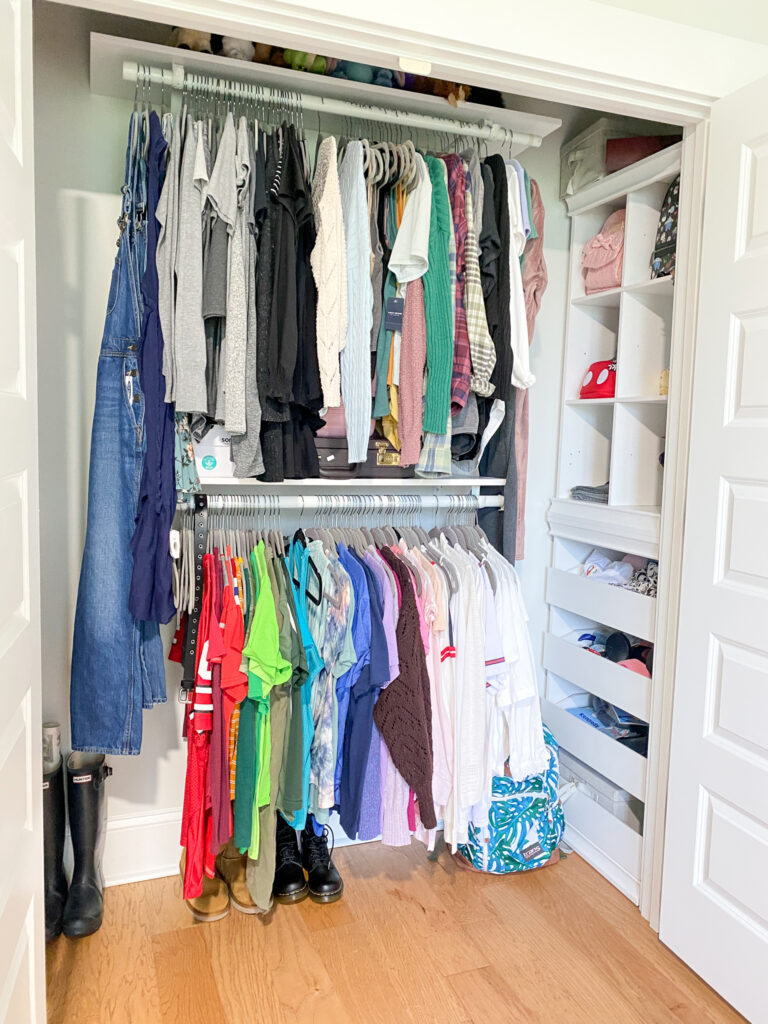 Open closet with two rows of hanging clothes, one row directly above the other. to the right of the hanging clothes is a tower or organizational shelving with various items inside.
