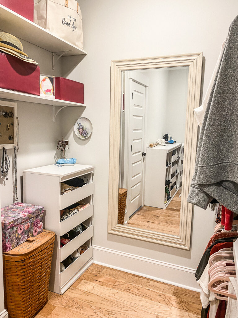 large mirror in the middle of the wall to the right of the mirror is hanging clothes. to the left of the mirror is a small white dresser and next to that is a woven hamper with a floral box on top. above the hamper and dresser is a small decorative flower plate and jewelry holder hanging on the wall. above are two shelves, but only one is visible completely. the shelf you can see has two dark pink boxes, one with a stack of hats on it and in between is a colorful piece of art.