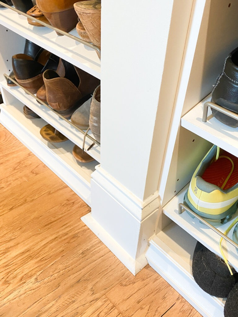 close up of the bottom of the separator wall showing how the closet system is sitting flush with the wall and the baseboard is surrounding it to give the closet system a built in look.