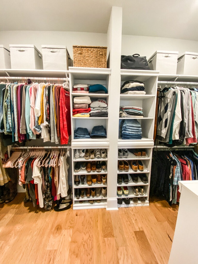 closet with a wall down the middle and on either side of the wall is a tower of shelving holding folded clothes and shoes. on either side of the tower are two rows of hanging clothes, one row directly above the other. on top of the top row of hanging clothes is a shelf and gray fabric covered storage boxes as wel as a woven basket and a black bag