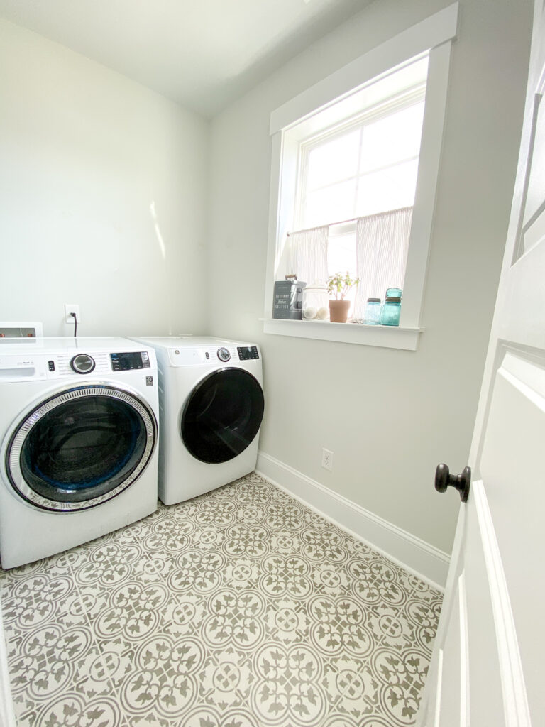 White door on the right with black door knob, opens to pretty empty laundry room. White washer and dryer to the left. The floor is gray and white floral design. On the window sill to the right of the dryer is a gray box, glass jar, plant, and three light blue glass jars.