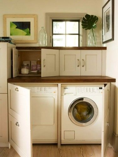 Inspiration photo fo a washer and dryer surrounded by a cabinet. Above the cabinet is a window and in front of the window are clear glass bottles, one with a green floral stem.