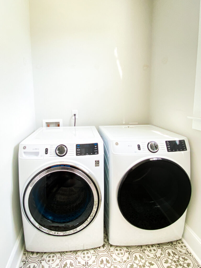 White washer in dryer with a gray and white floor. Up against a light gray wall with washer hook up and electrical outlet.